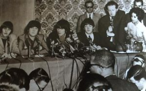 Tony Barrow (with mic) supervising a Beatles press conference.